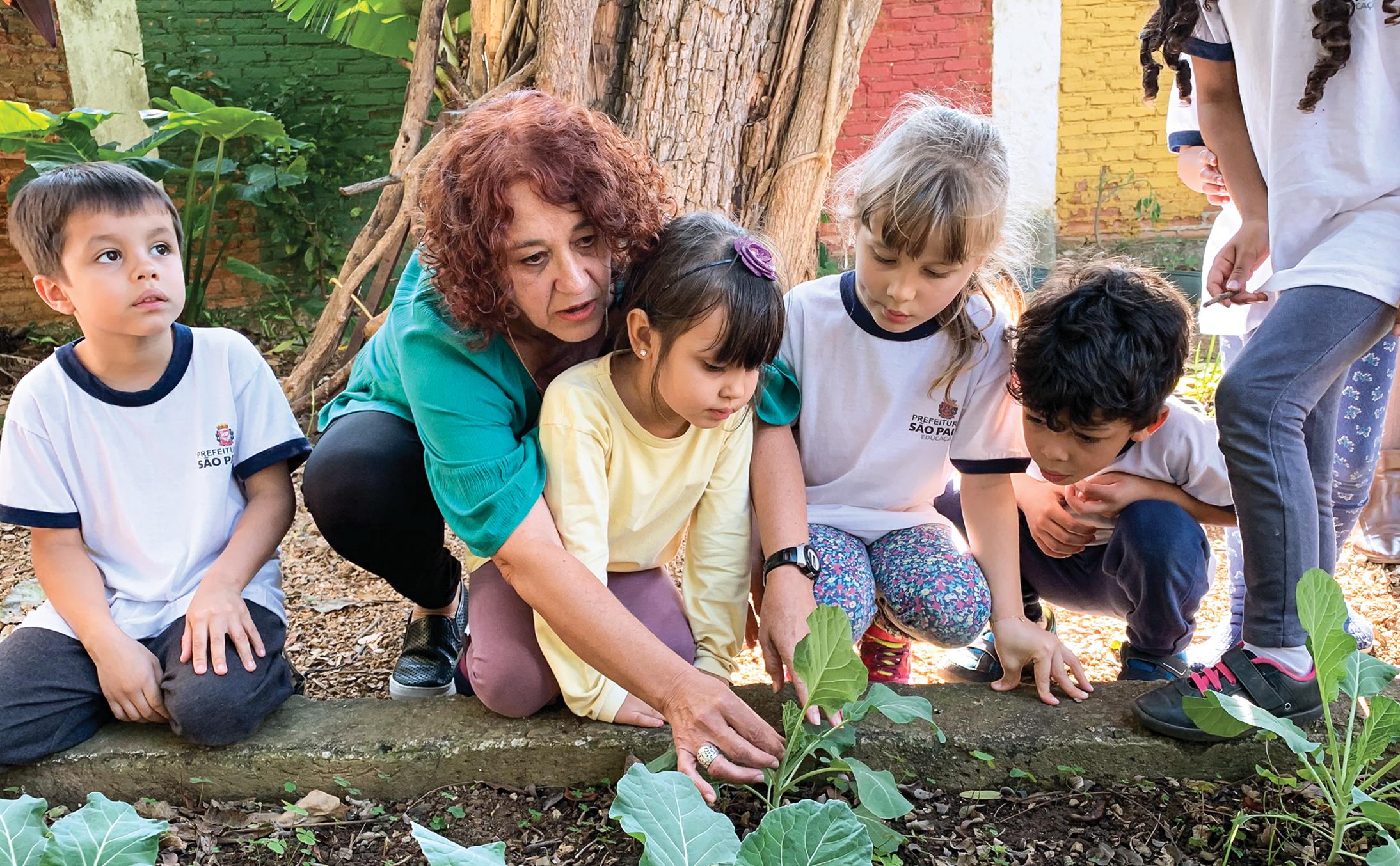 preschool teacher and students in garden